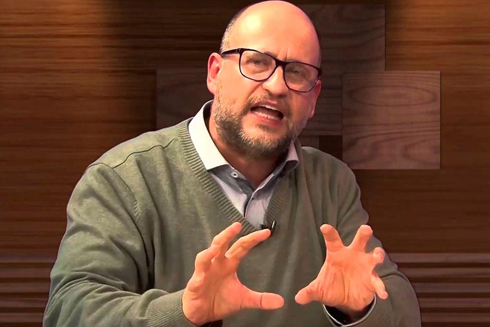 Homem discursando para dar ênfase no texto sobre ser carismático e cativar o público
